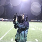 Junior Benjamin Cahoon operates a wireless camera at a football game