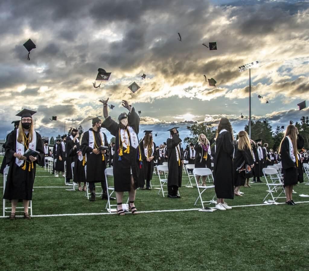 High school graduates throw caps into the air